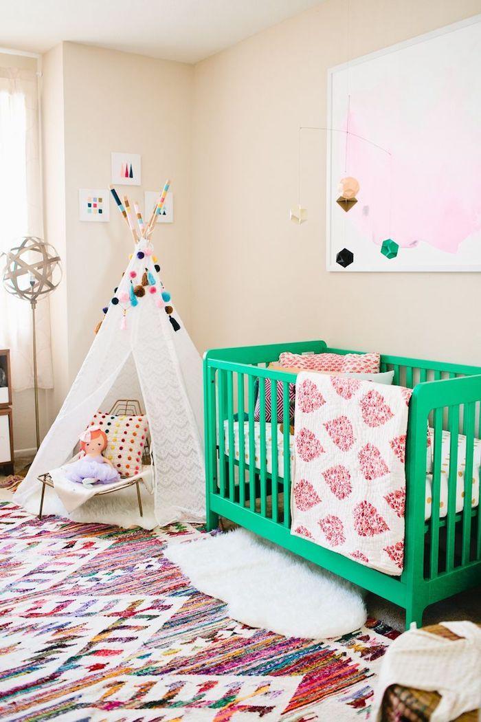 Babyzimmer Einrichtung, grünes Babybett aus Holz, weißer Zelt mit bunten Pompons verziert