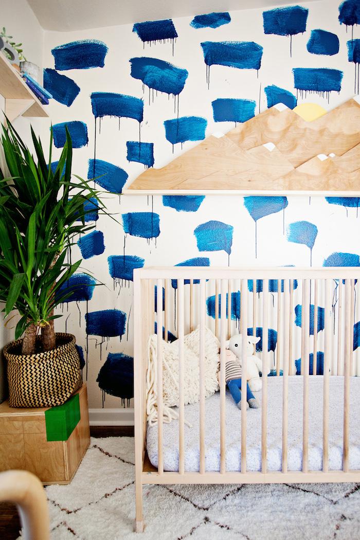 Babyzimmer im Vintage Stil, Babybett aus Holz, grüne Pflanze, Tupfetechnik an der Wand