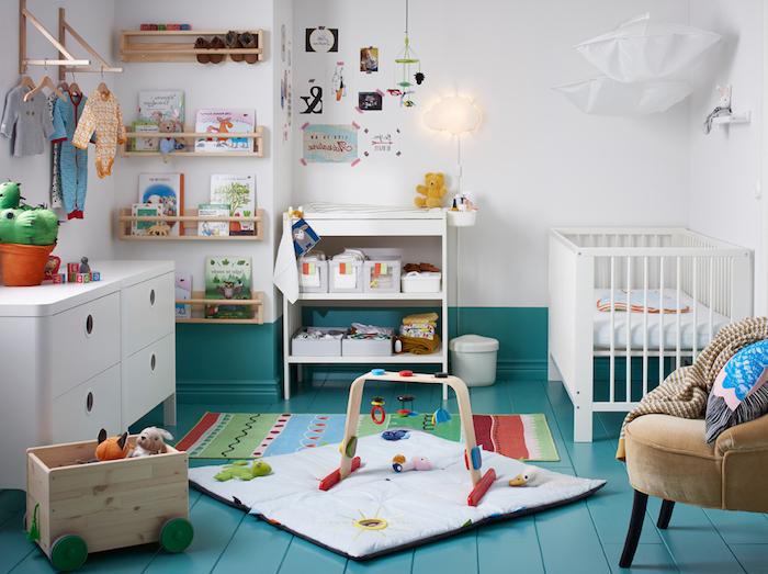 Babyzimmer Einrichtung, weiße Wandfarbe und blauer Boden, viele Spielzeuge, Kinderbücher und Babykleider