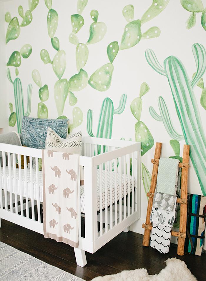 Babyzimmer Einrichtung, weißes Babybett, Holzleiter daneben, Tapete mit grünen Kakten