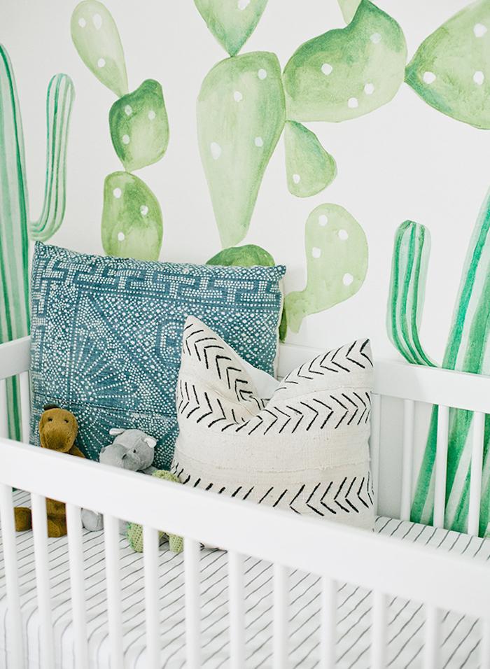 Weißes Babybett, zwei kleine Kissen und Kuscheltiere, weiße Tapete mit grünen Kakten
