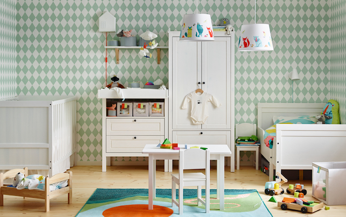 Babyzimmer in hellen Pastelnuancen, weiße Holzmöbel, Lampenschirme mit bunten lustigen Motiven. bunter Teppich, Bett für Kuscheltiere