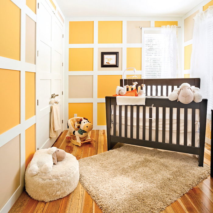 Babyzimmer in Gelb, dunkelblaues Holzbett, süße Kuscheltiere und Mobile
