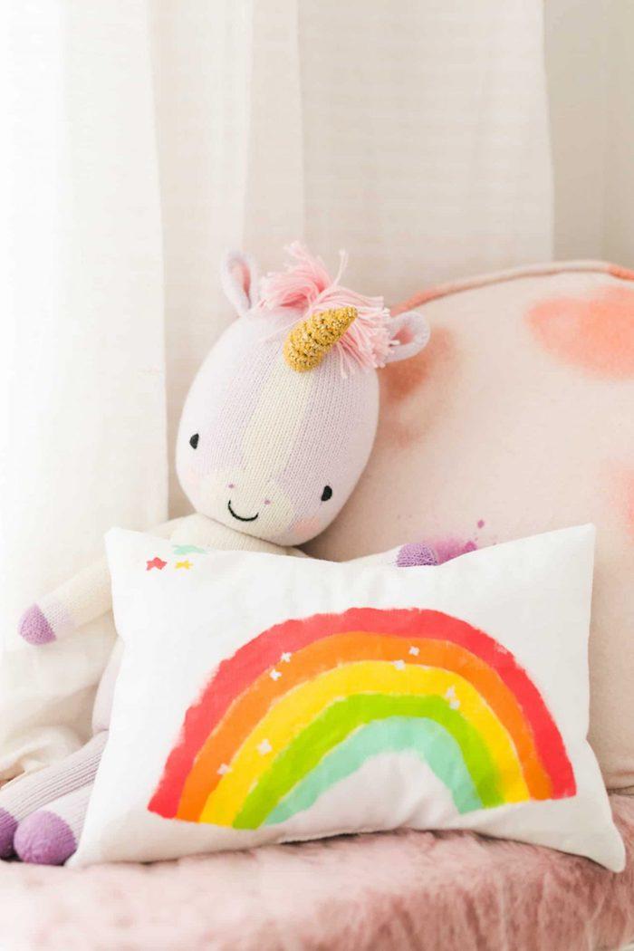 Babyzimmer Deko Ideen, weißes Kissen mit Regenbogen, Einhorn Plüschtier, rosa Bettwäsche