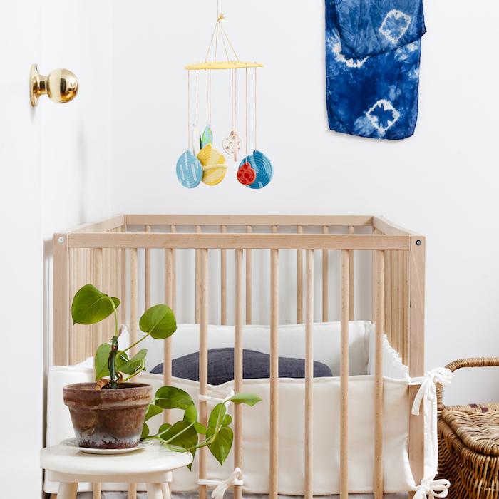 Babyzimmer in Vintage Stil gestalten, Babybett aus Holz, Rattan Stuhl, grüne Zimmerpflanze, bunte Mobile über dem Bett