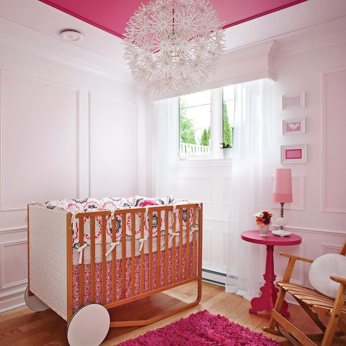 Mädchenzimmer für Baby, Holzbett mit Rollen, verspielter kronleuchter, violetter Teppich und Tisch