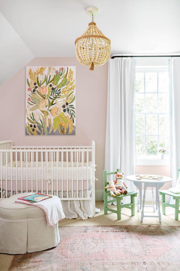 Babyzimmer in zarten Pastellnuancen, kleiner Tisch mit grünen Stühlen, weißes Babybett, Gemälde an der Wand