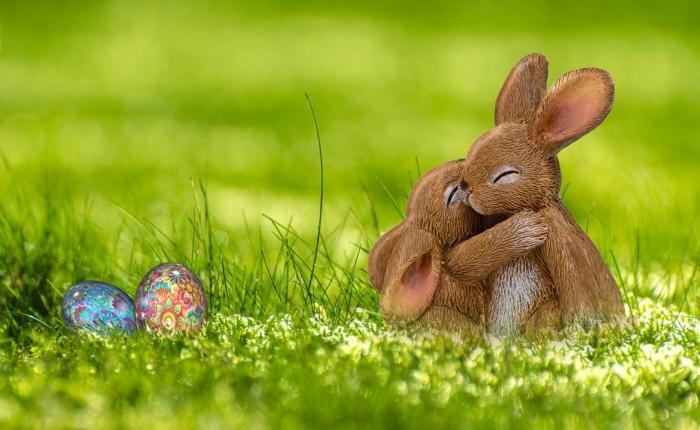 Ostereier färben, der Osterhase hat zwei Ostereier versteckt und seine Freundin umarmt ihn