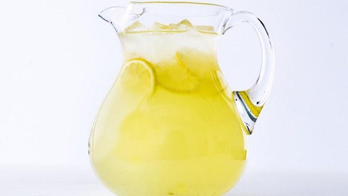 ein großer krug mit einer gelben hausgemachten limonade mit eis und mit vielen kleinen gelben zitronen, eine amerikanische limonade selber machen