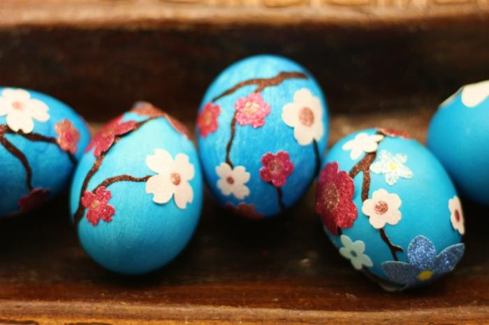 fünf blaue Eier mit kleinen Frühlingsblumen als Motive, Ostereier färben