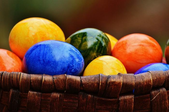 ein Körbchen voller bunte Eier, blau in Vordergrund, zwei gelbe und orange und grünes in Hintergrund