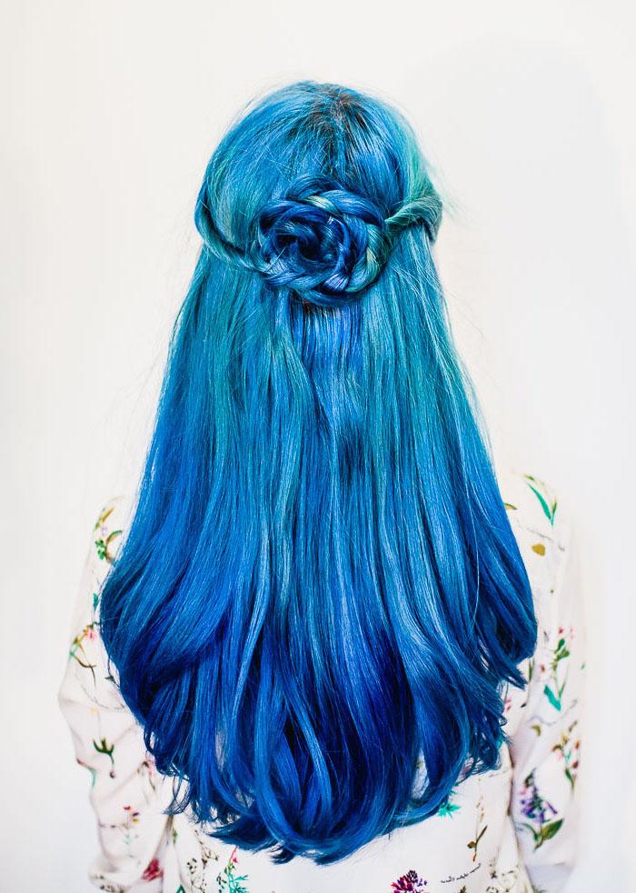 Blaue Haare, Langhaarfrisur mit Haarblume, zwei Blaunuancen, weißes Hemd mit Blumenmuster