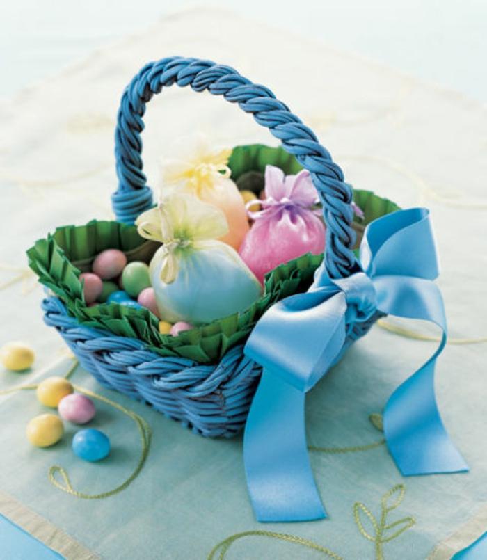 kleines blaues Körbchen mit blauer Schleife, voller kleine Ostereier, kleine Ostergeschenke