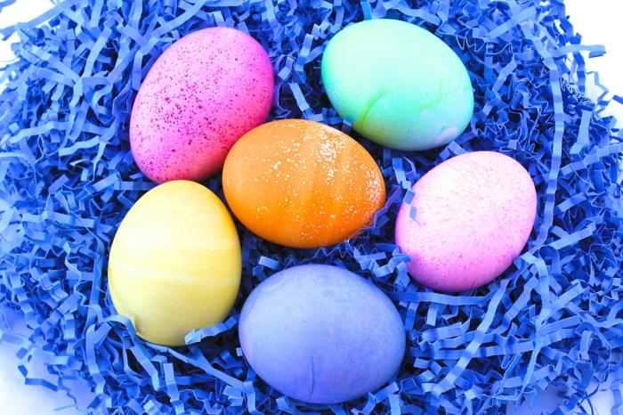Mit Kristalien Ostereier färben, helle Farben auf einem blauen Nest gelegt