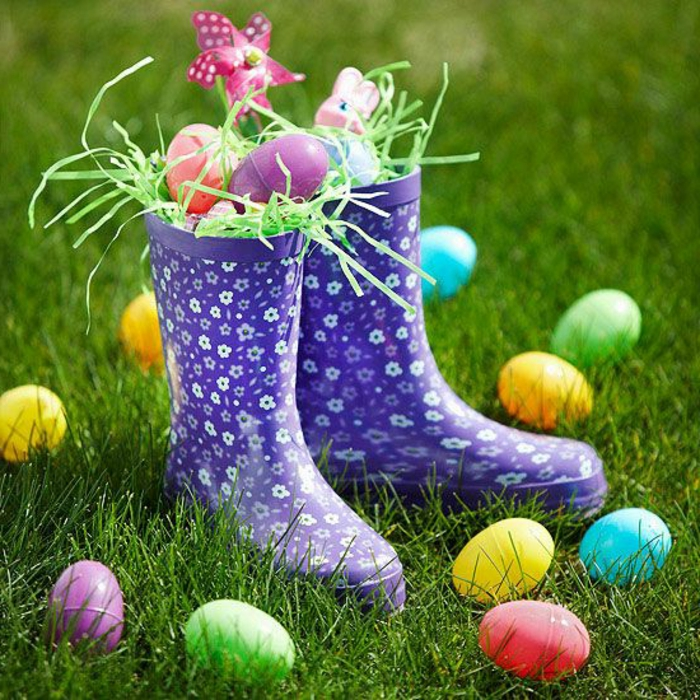 ein paar blaue Stiefel sind mit Ostereier voll, auf eine Wiese von Ostereier umgeben, Ostergeschenke basteln