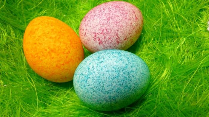 drei Eier in gelber, roter und blauer Farbe, Ostereier färben, Effekte mithilfe von Reis erzeugen