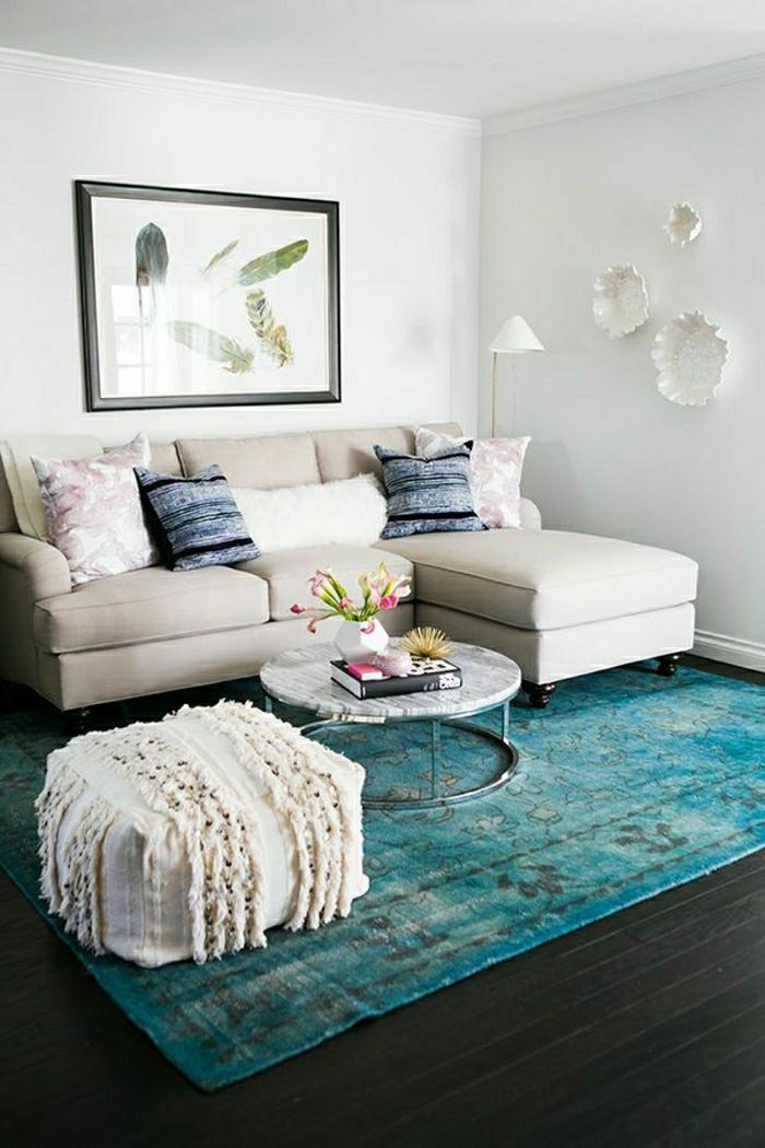 blauer Teppich, beiges Sofa, kleiner weißer Hocker, runder Tisch, Wohnzimmer gestalten