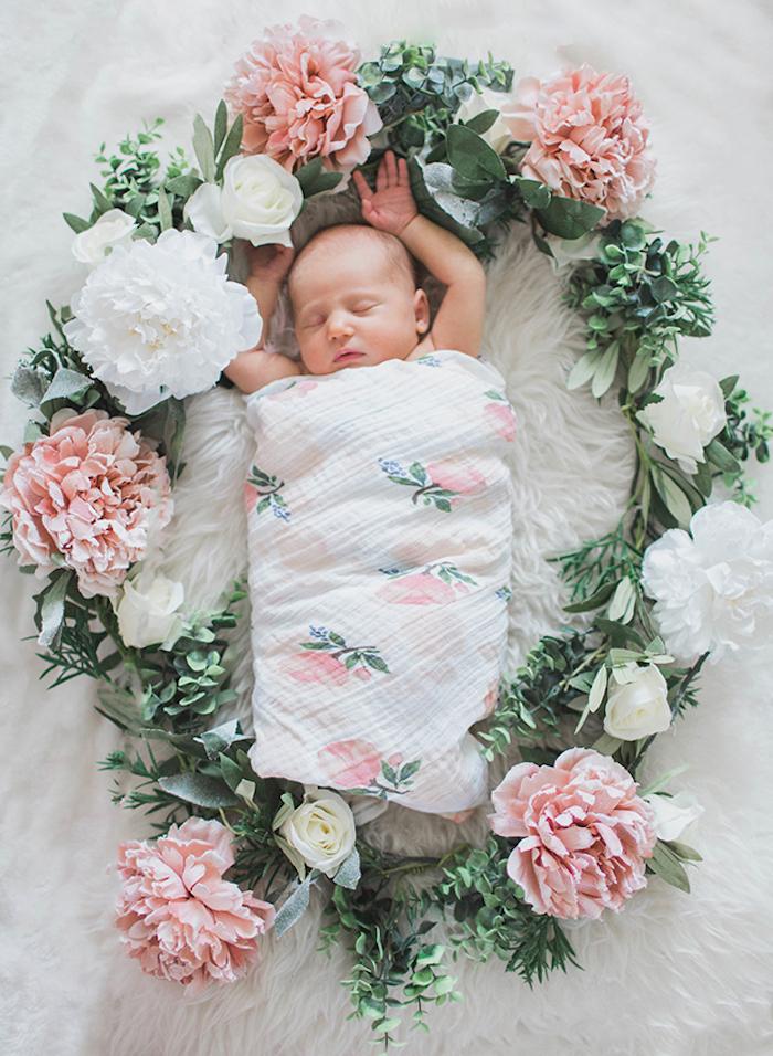 Süßes schlafendes Baby, Decke mit Blumenmuster, Kranz aus echten Blumen