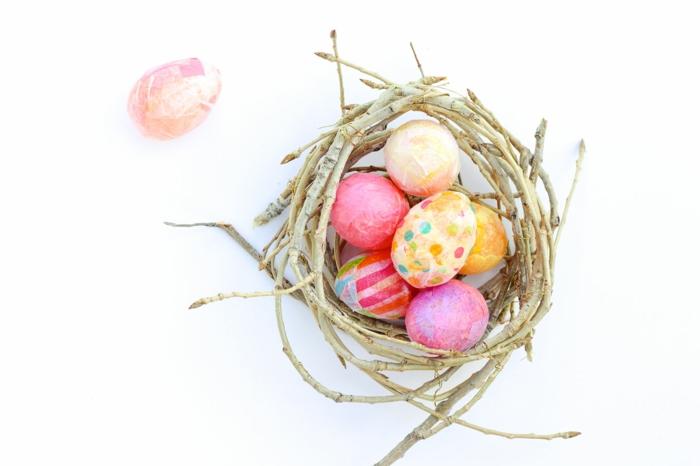 Ostereier färben und mit Papier umhüllen in ein Nest aus Stöcken legen