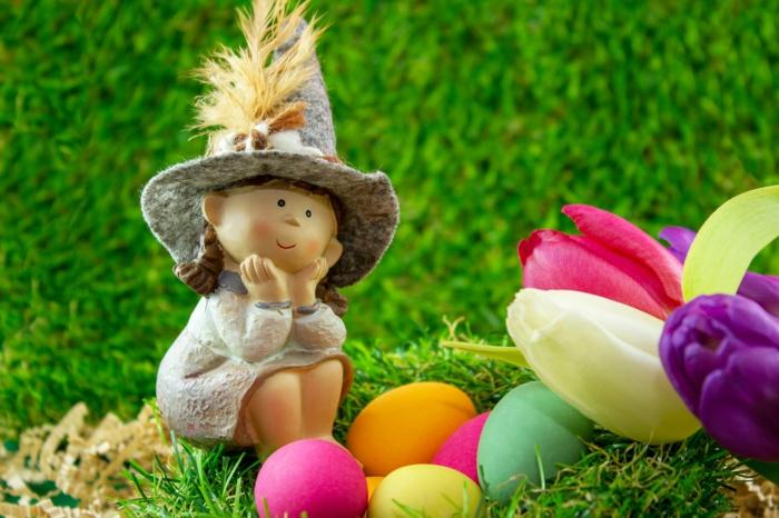 ein Gartenzwerg hat die Eier versteckt, bunte Eier und Tulpen, Ostereier natürlich färben