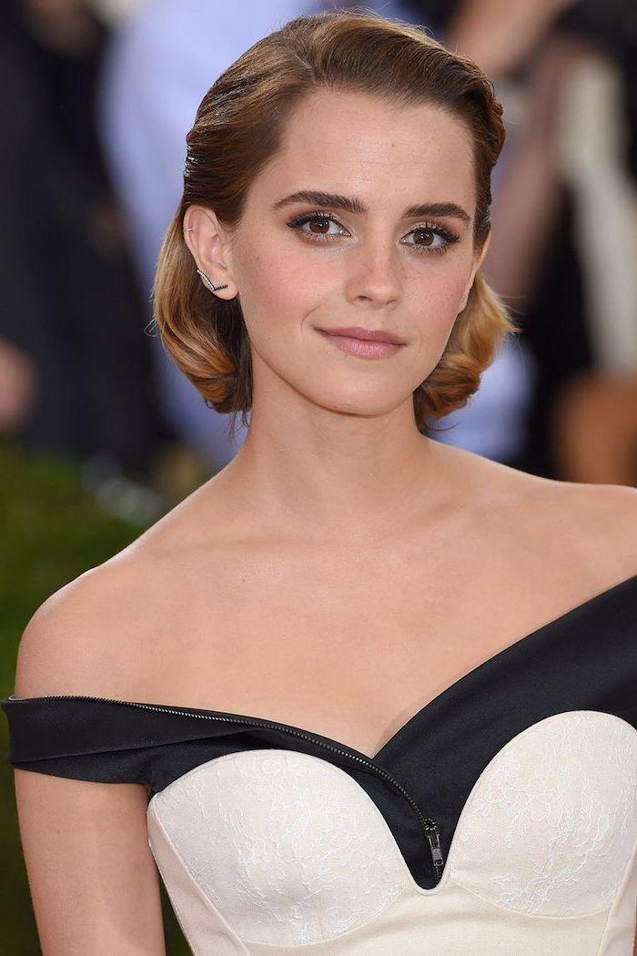 Emma Watson Kurzhaarfrisur, kastanienbraune Haare, schulterfreies Abendkleid, matter Lippenstift und schwarze Mascara