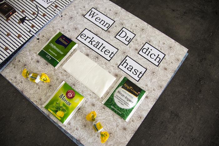 ein großes wenn buch mit drei grünen teearten, tee mit minze miz grünen blättern, zwei kleine gelbe bonbons und eine kleine weiße serviette, wenn buch sprüche