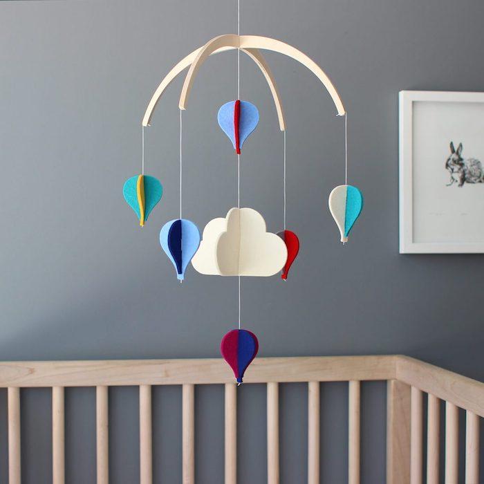 Mobile fürs Babyzimmer in Form von Wolken und Heißluftballons aus Filz, Wandfarbe Grau, Babybett aus Holz