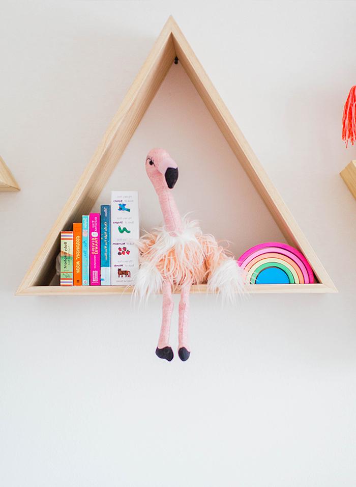 Dreieckiges Holzregal an der Wand, Plüschtier Strauß, Kinderbücher und kleiner Regenbogen