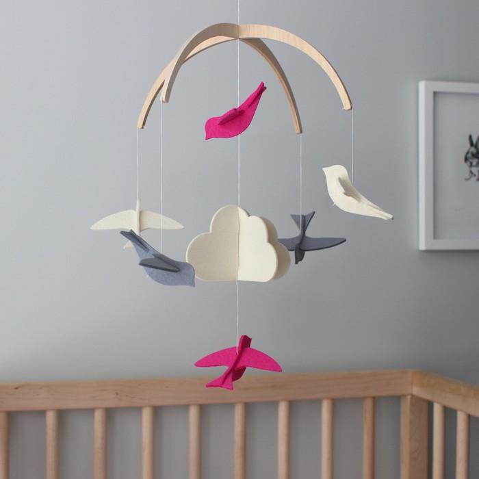 Mobile aus Filz, bunte Vögelchen und weiße Wolken, Babybett aus Holz, Wandfarbe Hellgrau