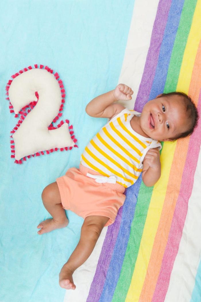 Weiße Plüschziffer mit roten Pompons, Bettwäsche als Regenbogen, süßes Baby mit kariertem Unterhemd und orange Hase