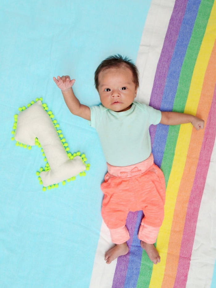 Weiße Plüschziffer mit gelben Pompons, Regenbogen Bettwäsche, süßes Baby mit hellblauem Shirt und oranger Hose