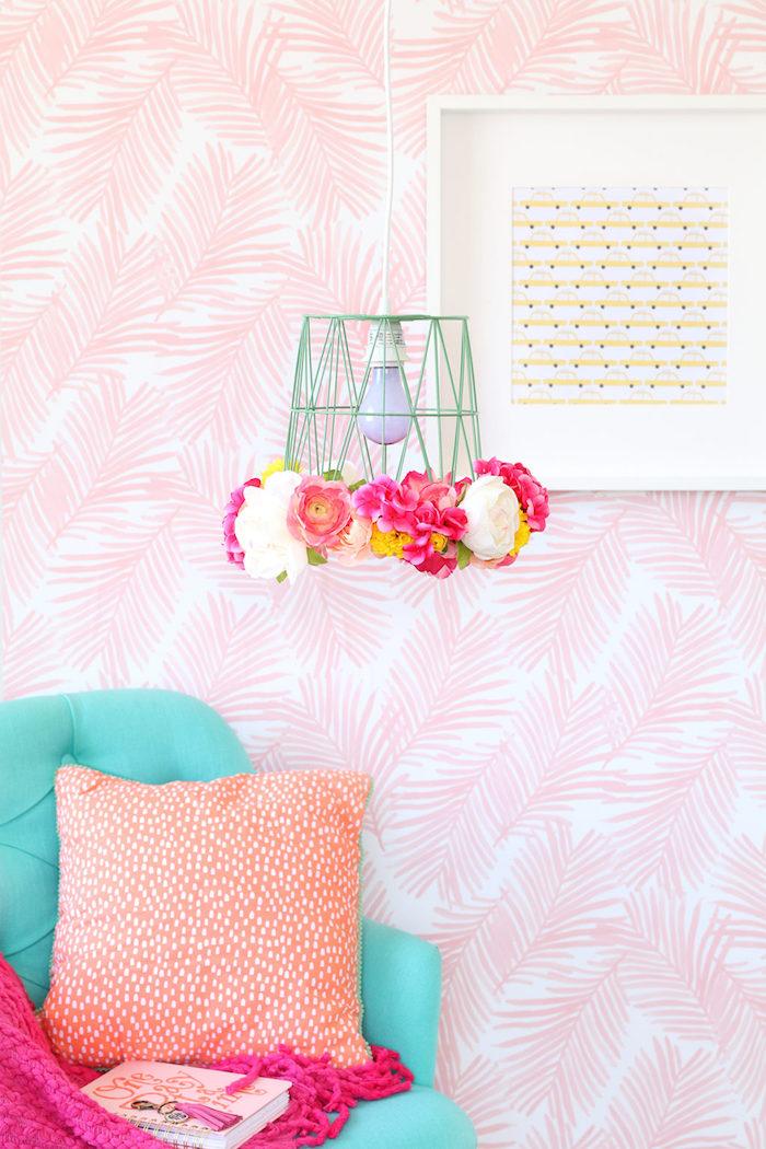 Lampenschirm mit künstlichen Blüten, Frühlingsdeko im Wohnzimmer, blauer Sessel, rosa Decke, Kissen mit weißen Punkten