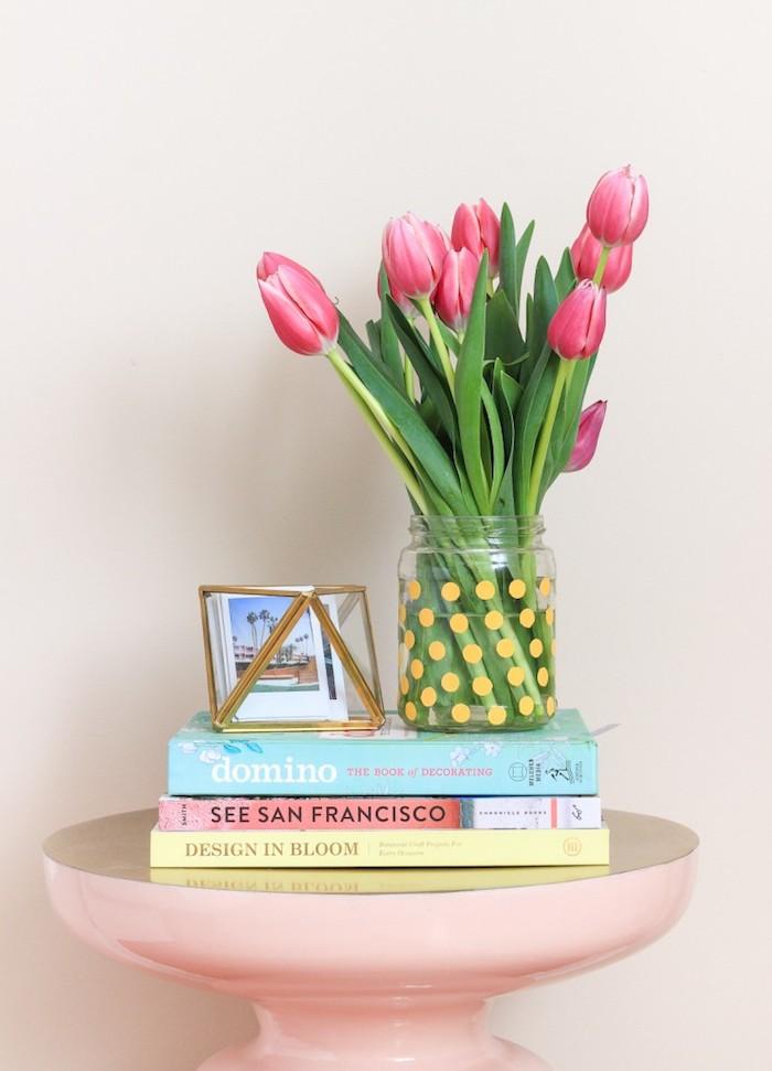 Tulpenstrauß in Einmachglas, gelbe Punkte, rosa Tisch, drei Bücher, kleine Fotos in Box