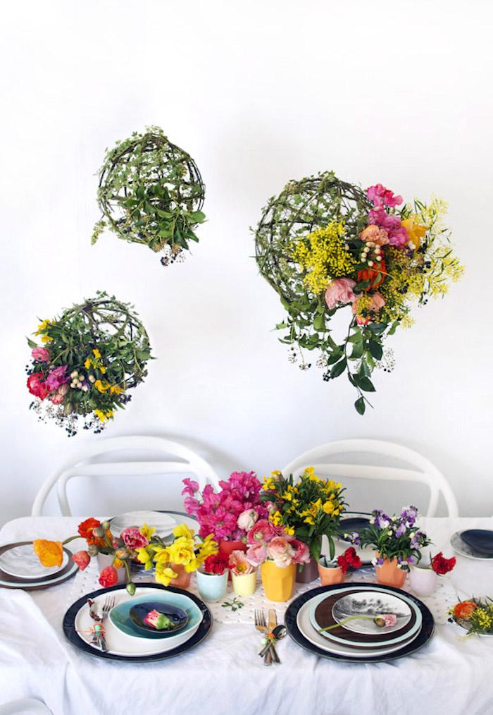 Grüne Kugeln mit bunten Blättern, Frühlingsdeko im Esszimmer, viele Blumen auf dem Tisch