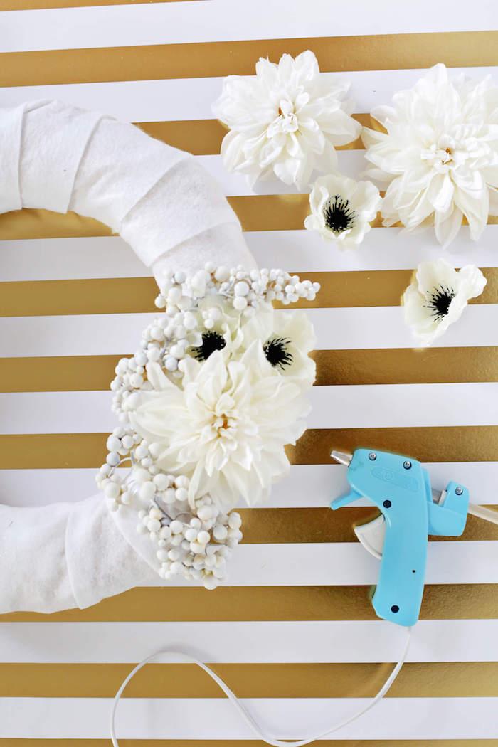 Türkranz selber machen, weiße Chrysanthemen mit Heißkleber befestigen, Frühlingsdeko für die Haustür