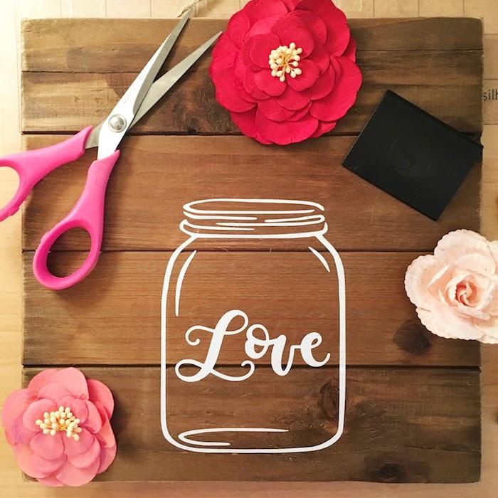 Bastelidee für Frühlingsdekoration, Einmachglas auf Holztafel zeichnen, mit Aufschrift Liebe, künstliche Blüten aufkleben