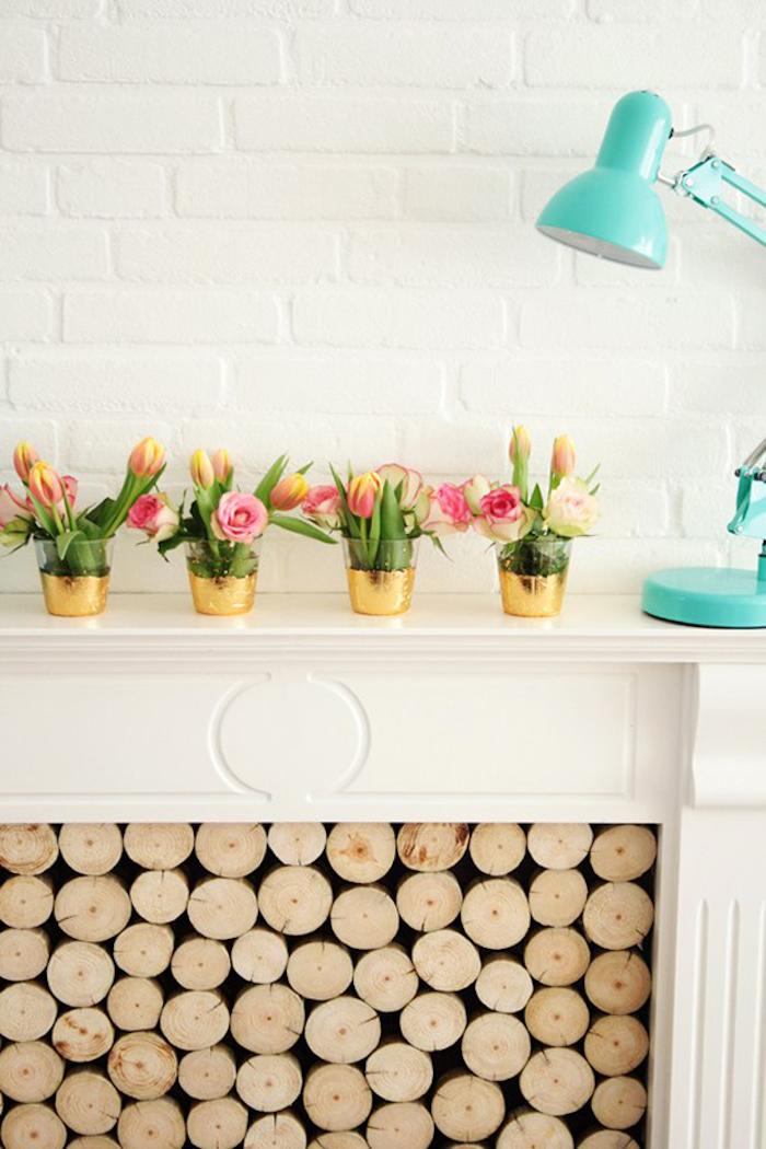 Gläser mit goldenem Glitzer verzieren, Rosen und Tulpen, Deko auf weißem Kamin, blaue Nachttischlampe