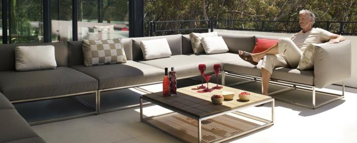 terrassenumrandung mit sofa und möbel, schöne idee, mann sitzt auf der eigenen terrasse und genießt den tag
