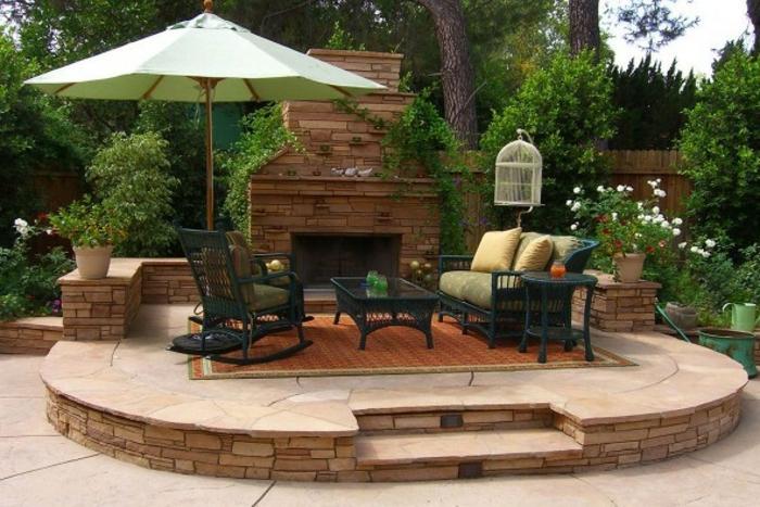 terrasse dekorieren, sitzecke auf der terrasse, sonnenschirm idee, kamin, bequem, gemütlich