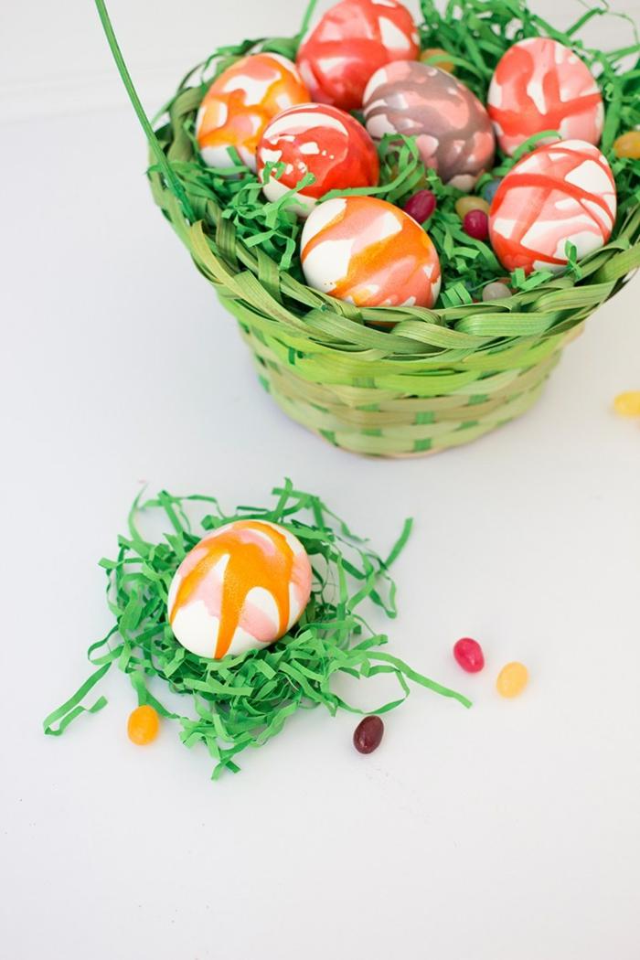 ein Nest mit künstlicher Gras und ein bemaltes Ei darin, Ostereier dekorieren