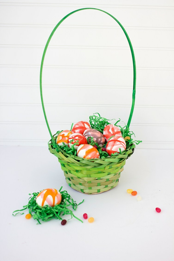 grünes Körbchen mit künstlichem Gras, bunte Eier, Ostereier dekorieren