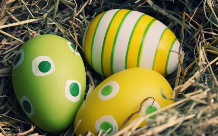 Ostereier natürlich färben in ein Nest gelegt, grüne, weiße und gelbe Eier