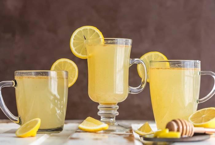 drei gläser mit einer hausgemachten gelben limonade mit vielen kleinen gelben zitronen, eine limonade selber machen