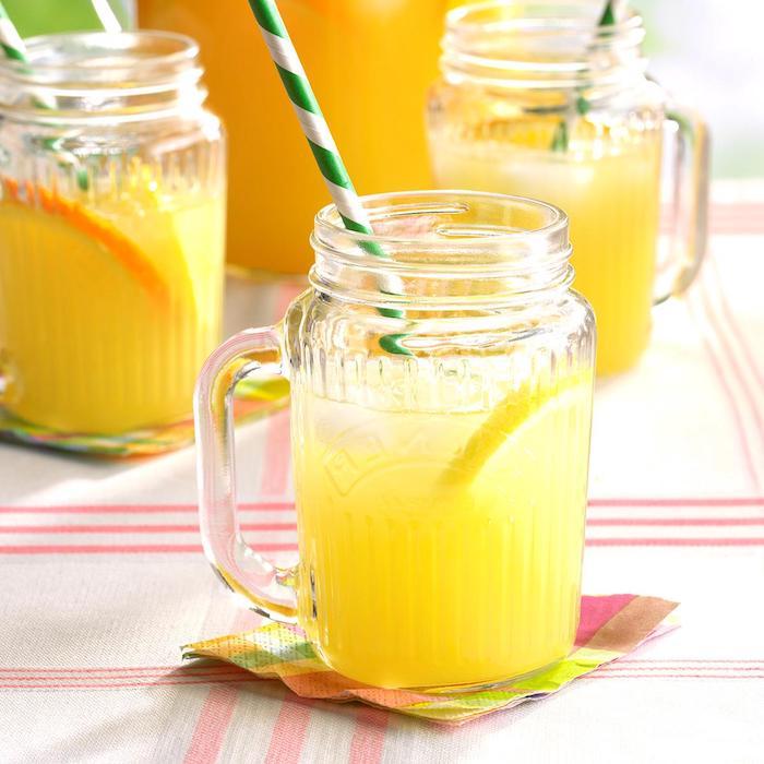 drei große gläser mit einer gelben hausgemachten limonade mit vielen kleinen zitronen und eis und einem großen grünen strohhalm, eine limonade selber machen