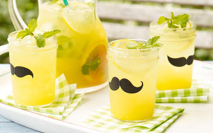 ein krug mit einer selbstgemachten limonade mit einer minze mit grünen blättern, eis und vielen kleinen gelben zitronen, drei gläser mit einer amerikanischen zitronenlimonade und mit schwarzen selbstgebastelten schnurrbärten, ein krug mit einem blauen strohhalm