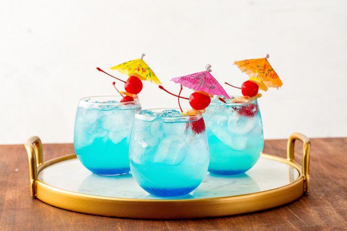 ein tisch aus holz und drei kleine gläser mit einer blauen limonade mit eis, kleinen roten kirschen und mit kleinen gelben, orangen und violetten cocktailschirmchen, eine erfrischungsgetränk selber machen