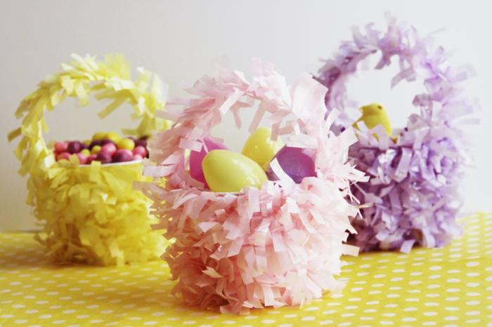 aus Papier Ostergeschenke basteln, drei Körbchen mit buntem Papier verschönert und mit Süßigkeiten befüllt