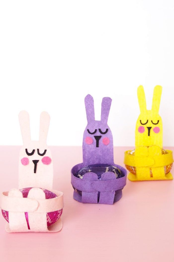 drei diy hasen ais papier, osterbilder kosstenlos herunterladen, pinke, gelbe und violette hasen mit schwarzen augen, drei ostereier und ein pinker tisch