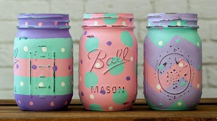 zu Ostern dekorierte Weckgläser in lila, grüner und rosa Farbe, Ostergeschenke basteln