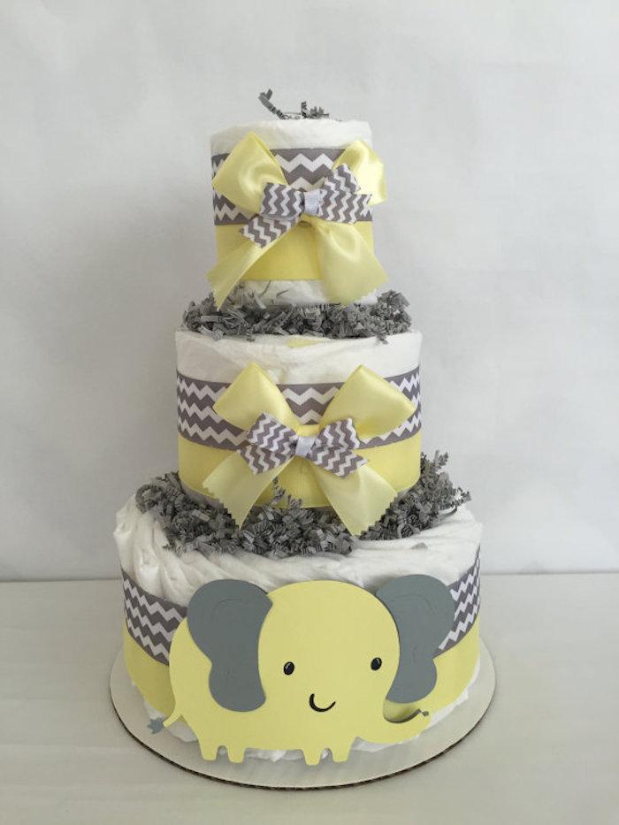 ein großer gelber elefant mit großen grauen ohren und schwarzen augen, eine dreistöckige torte mit großen gelben und kleinen grauen schleifen, eine windeltorte selber machen